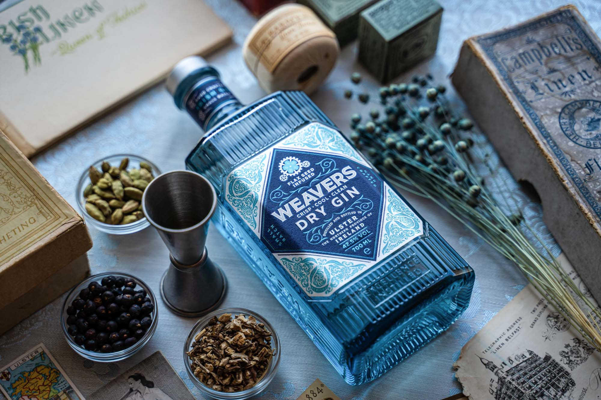 Weavers Gin bottle on linen tablecloth with botanicals and linen artefacts